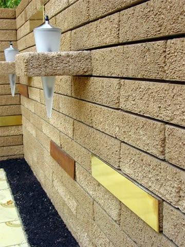 gartenmauer gelb aus naturstein mit wandleuchten als dekoration