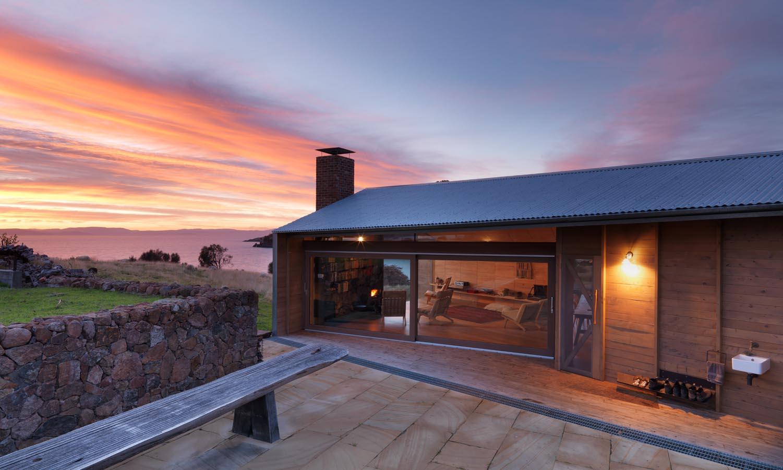Holzhaus mit Terrassenüberdachung und Terrassengestaltung mit Naturstein