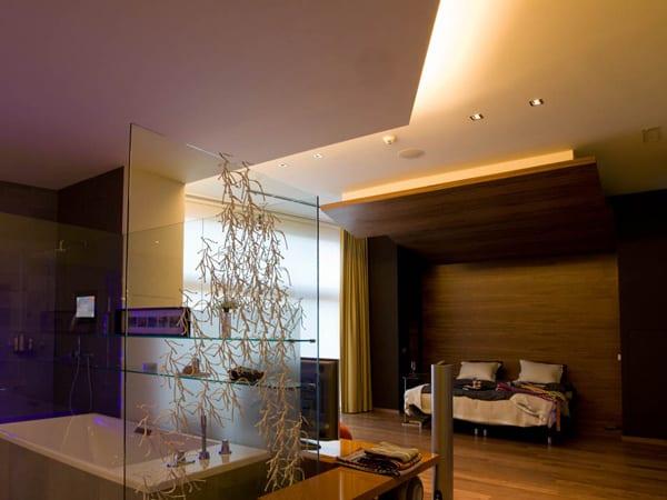 luxus schlafzimmer in wandnische aus holz mit offenem badezimmer mit wadewanne und glaswand