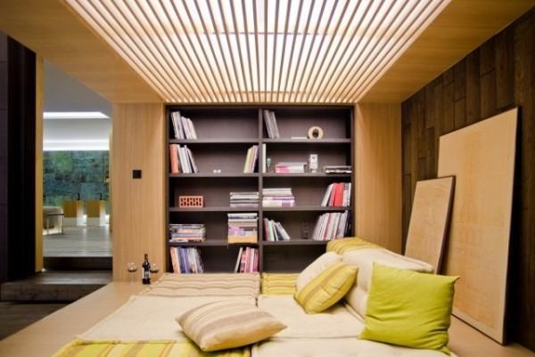 wohnzimmer einrichten mit wingebauten bücherregalen und Sitzecke aus Bodenkissen grün