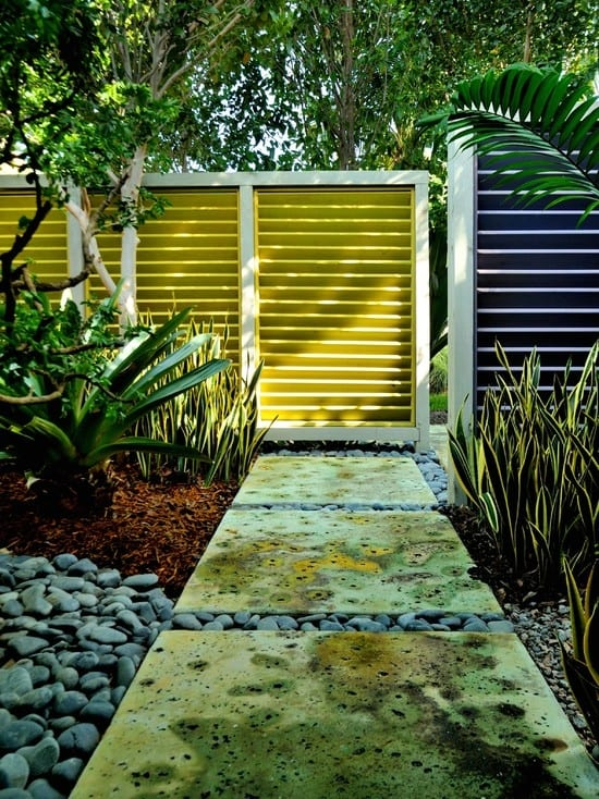 coole gartengestaltung mit steinplatten für den gartenweg und sichtschutz aus Holzwand in gelb und blau gestrichen