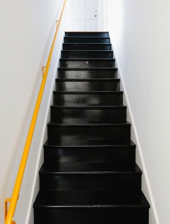 moderne treppe in schwarz mit gelbem wand-handlauf
