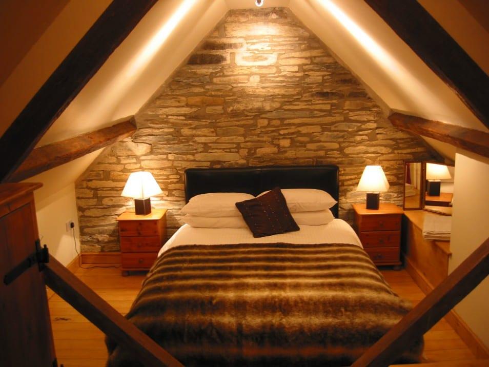 kleines schlafzimmer dachschräge mit holzboden und Lederbett schwarz