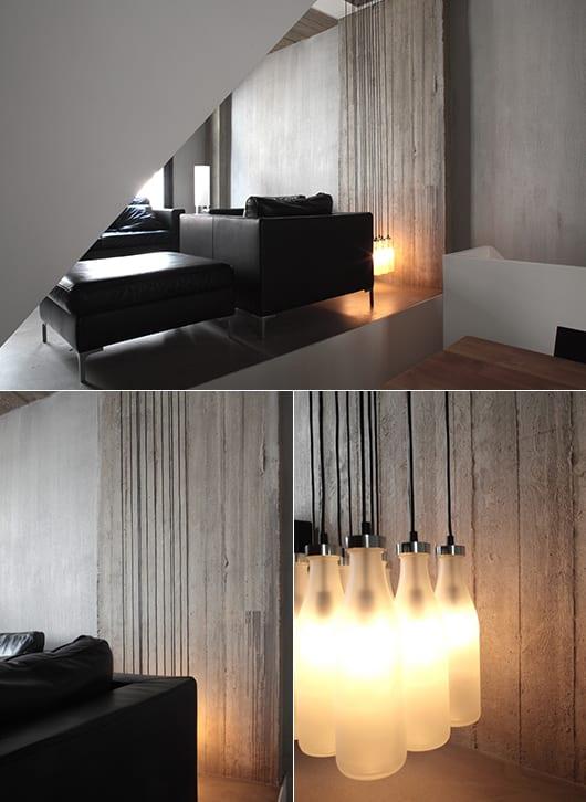 minimalistisches modernes wohnzimmer aus beton mit schwarzen Ledermöbeln und coole Pendellampe aus Glasflaschen