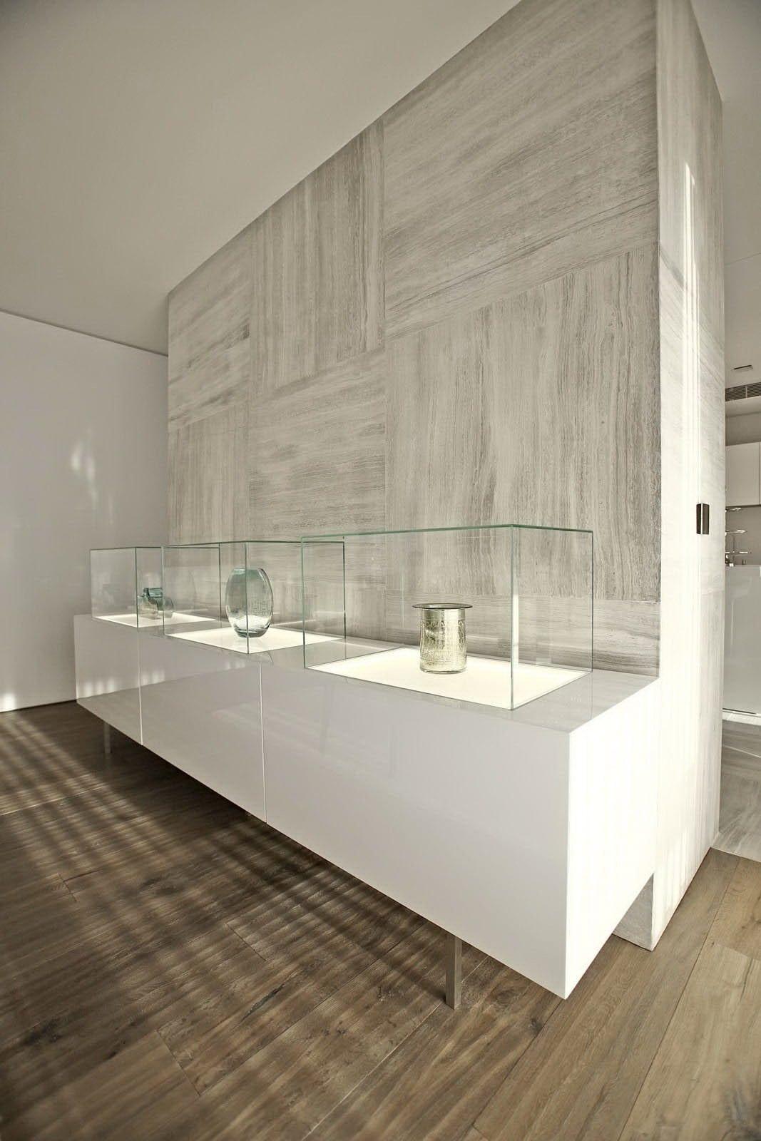 Wandgestaltung mit hellgrauen Marmorplatten und sideboard dekorieren mit schaukasten und indirekter beleuchtung