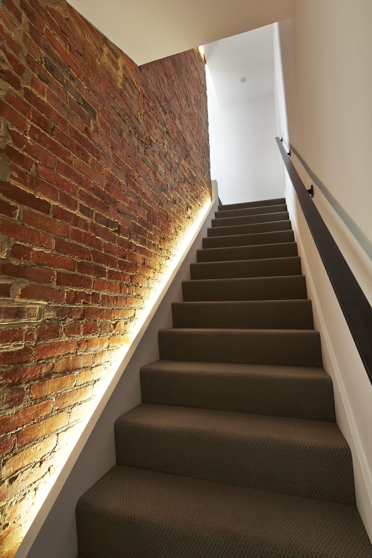 moderne innentreppe als wangentreppe weiß seitlich beleuchtet
