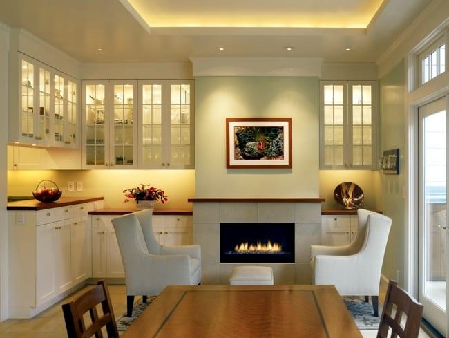 modernes wohnesszimmer mit kamin und esstisch massiv_wandfarbe hellgrün kombiniert mit weißen schränken