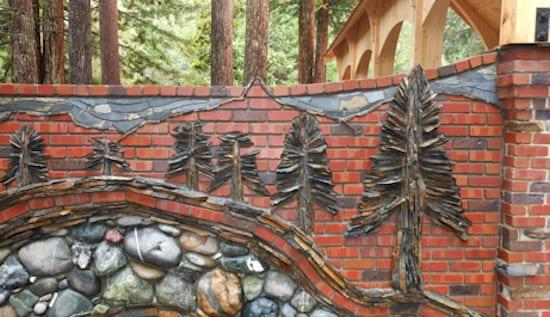 rote gartenmauer aus ziegeln mit dekoration aus gemörtelten Natursteinen