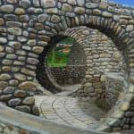 Gartenmauer als Mörtelmauer mit rundem Durchgang als coole Gartengestaltung und idee für Gartenwege