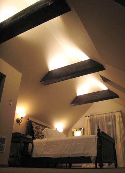 schlafzimmer dachschräge mit sichtbaren deckenbalken und dachfenster