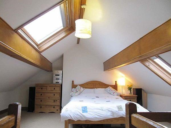 schlafzimmer dachschräge mit dachfenster und holzbett