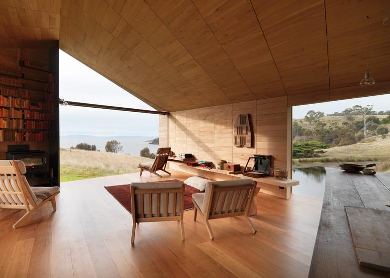 moderne einrichtung wohnzimmer mit holzsesseln und wandregal aus holz  als wanddeko