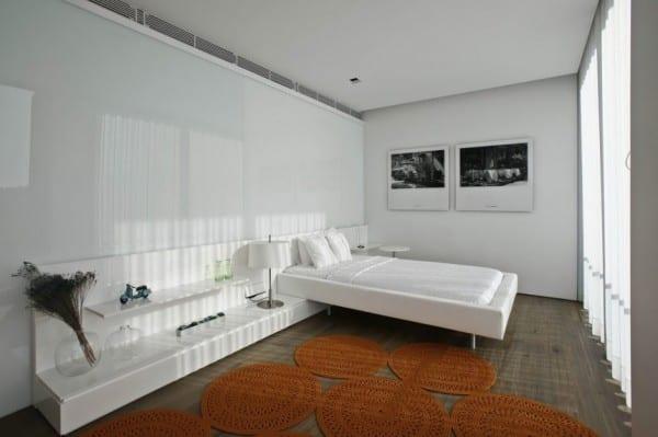 moderne schlafzimmer mit holzfußboden und bett mit sideboard in weiß
