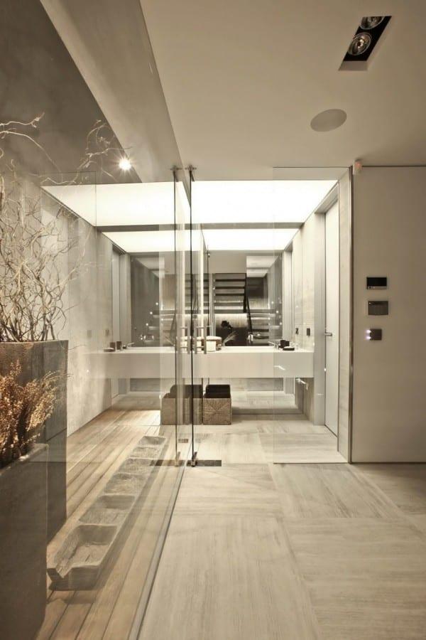 moderne Architektur mit glaswänden und wandspiegel im badezimmer mit waschtisch weiß