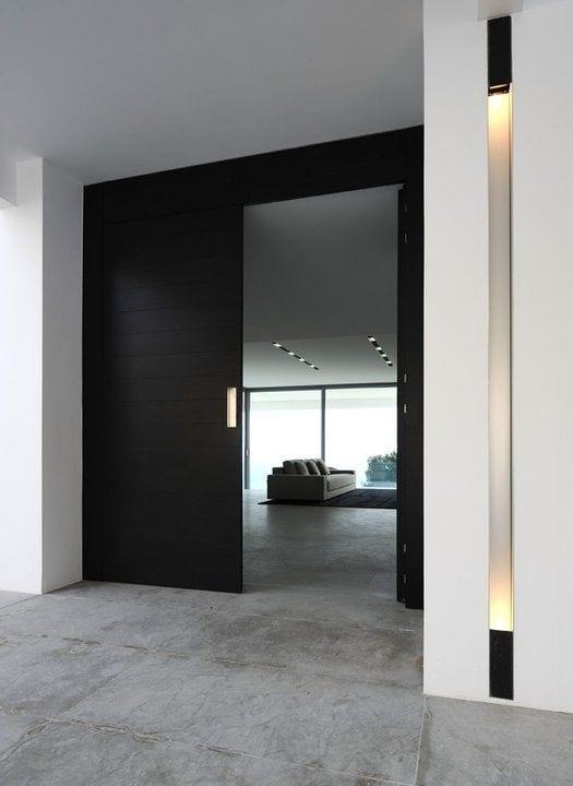 modernes haus mit eingangstür schwarz und eingebaute wandleuchte
