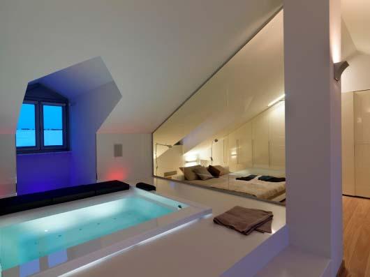 modernes schlafzimmer dachschräge mit Raumtrennung durch glasscheibe zwischen bettnische und badewanne