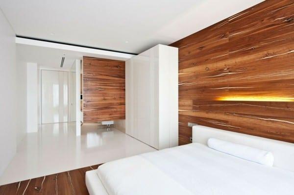 moderne schlafzimmer mit bett und kleiderschrank in weiß und wandgestaltung mit holz und wandleuchte für indirekte beleuchtung schlafzimmer