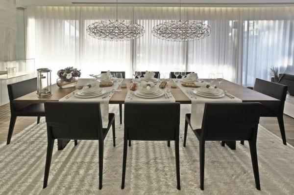 esszimmer einrichtung mit esstisch aus holz und lederpolsterstühlen in schwarz auf weißem Teppich