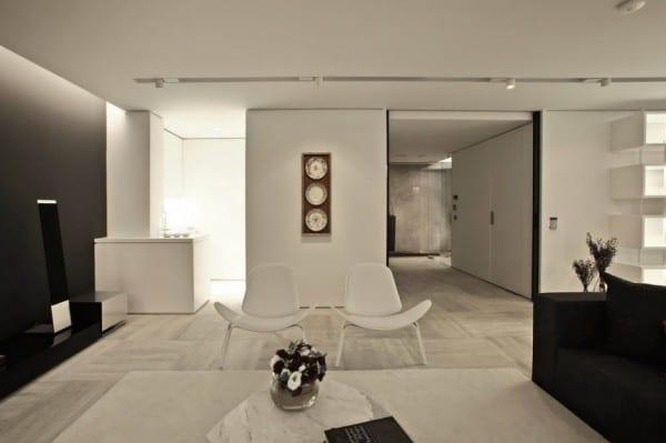 moderne wohnzimmer mit schwarzen wand und sofa und moderne weiße sesseln