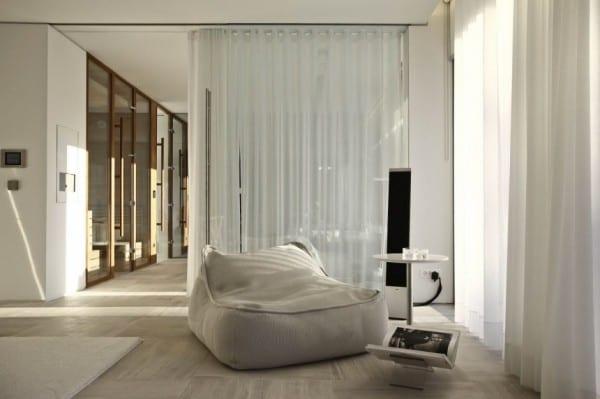 raumgestaltung mit weisem polstesessel und weißen gardinen