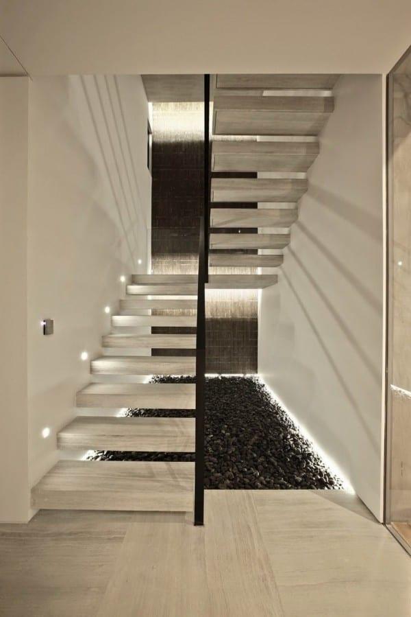 moderner treppenraum mit treppenstuffen aus maturstein und seiliche wandbeleuchtung