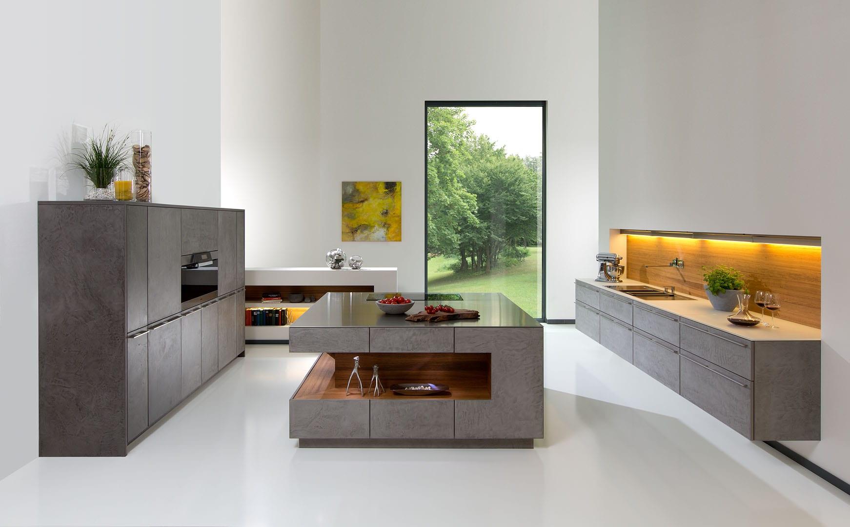 kochinsel beton  mit holznische und beleuchtung als teil moderner küche mit hängeschränken aus beton