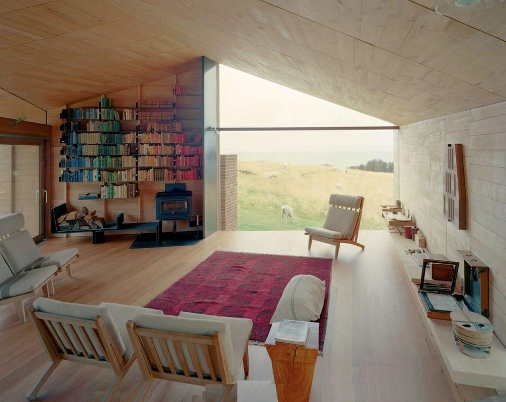 schicke wohnzimmer einrichtung mit möbelstücken aus holz und schwarzen Bücherregalen aus Blech