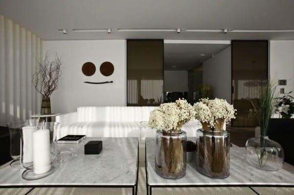 couchtisch deko idee mit kerzen und glasvasen mit blumen für luxus wohnzimmer schwarz-weiß