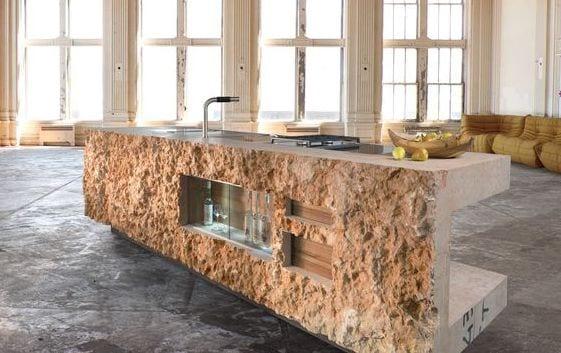 luxus küche mit betonboden und kochinsel aus naturstein mit eingebaiter vitrine für Weinflaschen