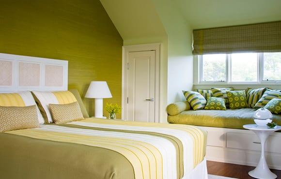 schlafzimmer dachschräge mit wandfarbe grün und bettdecke grün gemütlich gestalten_fensterbank als sitzplatz mit grünen kissen dekorieren