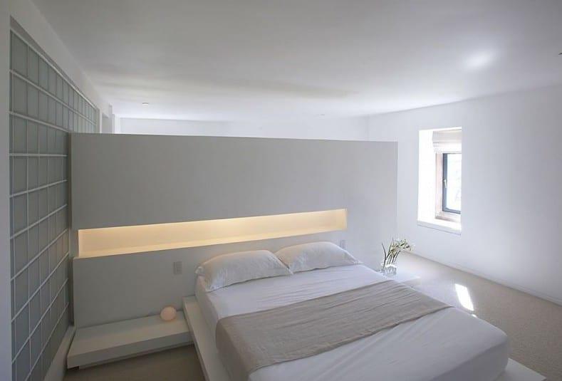 moderne schlafzimmer interior in weiß mit wand aus glassteinen und trennwand mit beleuchteter wandnische