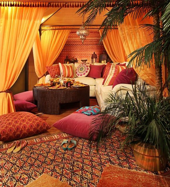 pergola mit gardinen und sitzecke mit rosafarbigen bodenkissen als gestaltungsidee für die terrasse