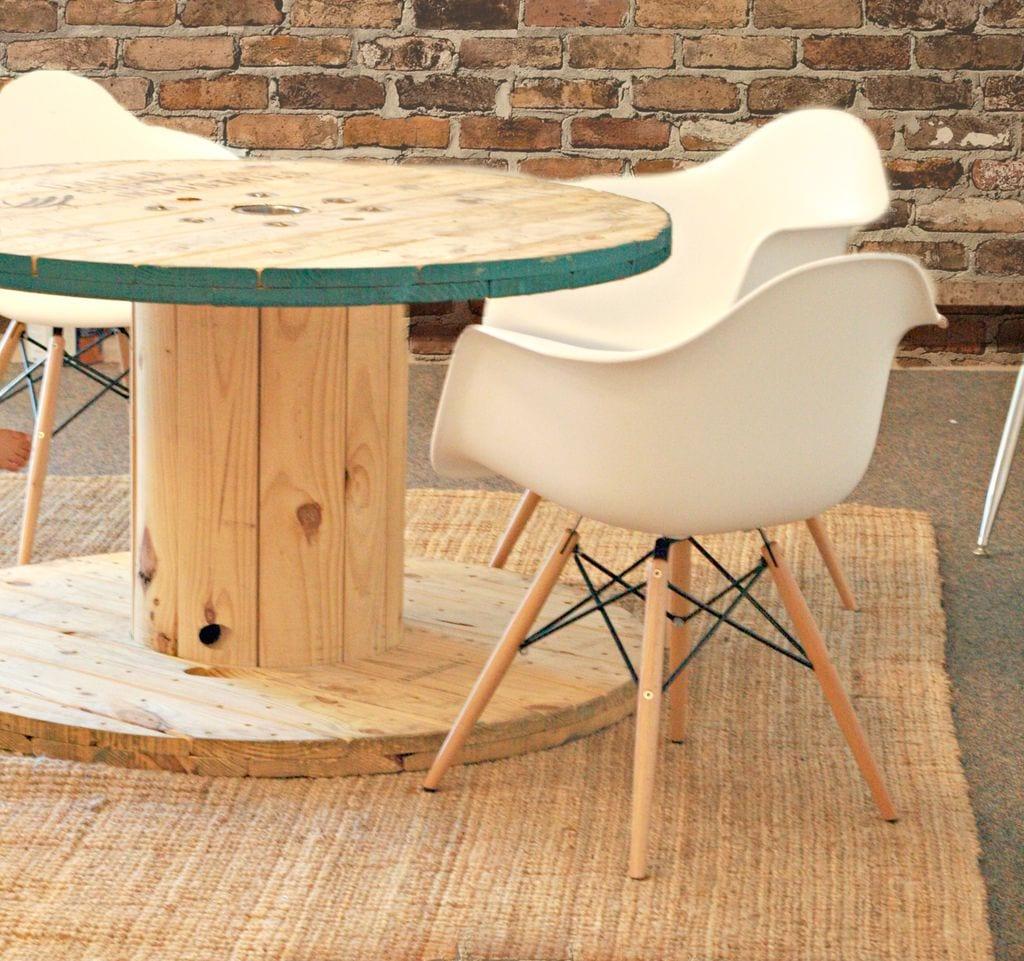 esstisch rund aus holz mit weißen esszimmerstühlen für wohnesszimmer interior mit ziegelwand und teppich beige