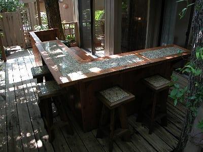 Holzterrasse gestalten mit Bar und Barhockern aus Holz mit Mosaikdekoration