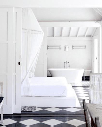 schlafzimmer mit badewanne und baldachin in weiß mit schwarzem bodenbelag holz