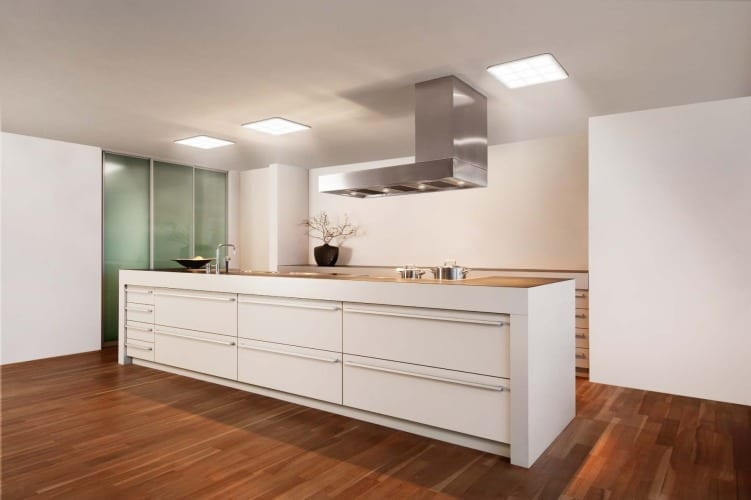 moderne küche in weiß mit parkett und quadratischen Deckenleuchte und abzugshaube über kochinsel
