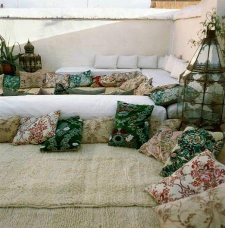 coole und moderne terrassengestaltung mit teppichen und bodenkissen in weiß und grün