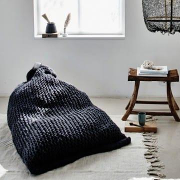 Vintage Interior mit rustikalem holzhocker als beistelltisch und weißem teppich mit bodenkissen sack in schwarz