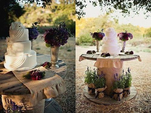 traum hochzeits deko rustikal mit Beisteltisch rund für die Hochzeitstorte mit lila Feldblumen und leinsacktischdecke