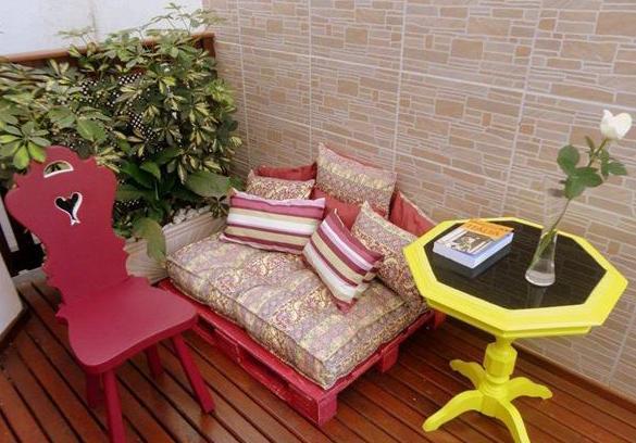 Holzterrasse modern gestalten mit rundem Holztisch gelb und DIY Sofa aus Europaletten in pink