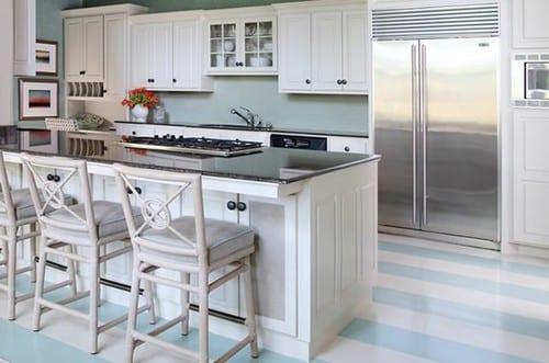 weiße küche mit kochinsel und wandfarbe blau und kreative bodengestaltung