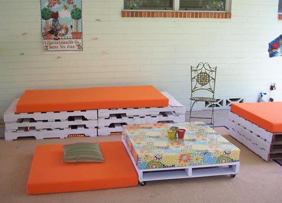 weiße paletten mit orangen bodenkissen als idee für coole terrasseneinrichtung