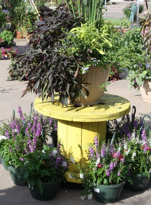 Terrassen- und Gartendeko mit Blumen und Kabelrolle aus Holz in gelb gestrichen