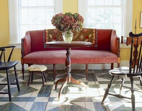 vintage wohnzimmer mit rustikalen mäbeln und sofa in rot mit couchtisch rund
