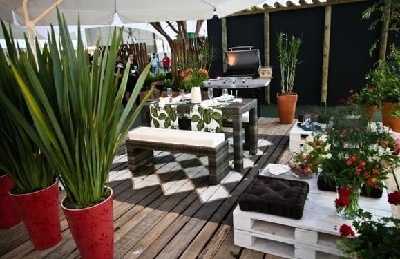 moderne terrasse mit holzboden und roten blumentöpfen einrichten