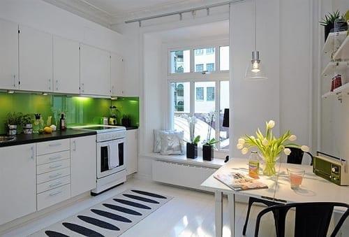 moderne weiße küche mit holzboden und esstisch weiß und grüne wand