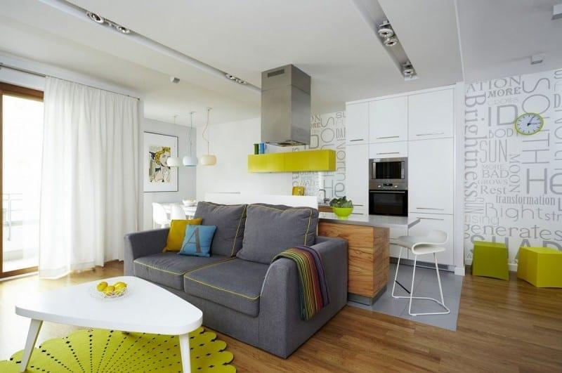 moderne wohnzimmer mit küche und Holzbar in weiß und grün gestaltet mit schriftzug tapeten weiß und sofa grau