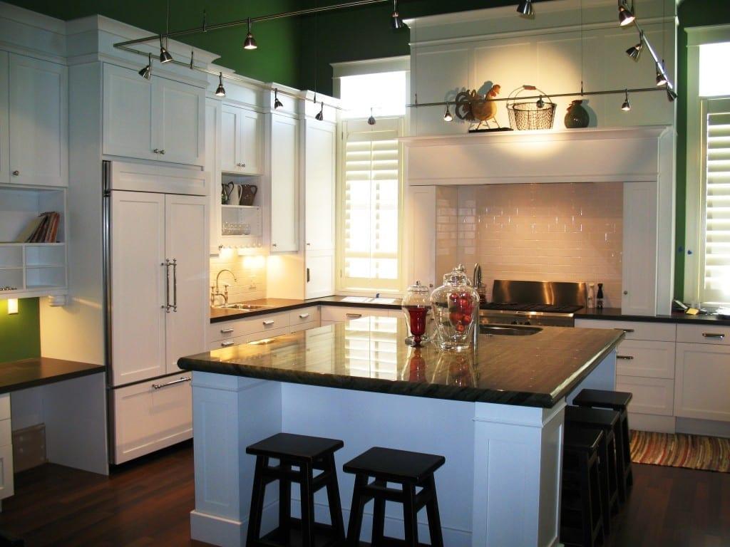 weiße küche mit quadratischer Kochinsel mit schwarzer granitplatte und schwarzen barhockern aus holz