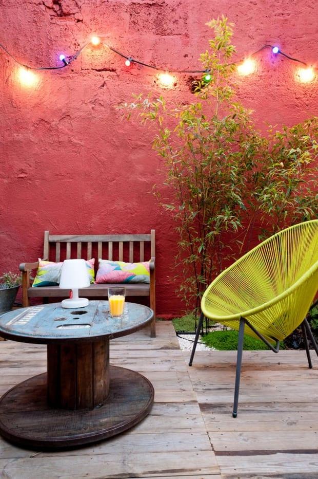 runder couchtisch holz für rustikale terrassengestaltung mit holzbank und sessel gelb als akzent zu der rosa wandfarbe mit leuchten
