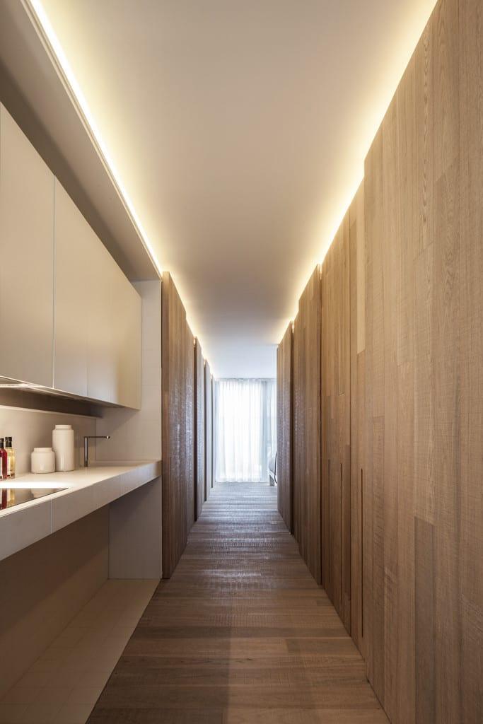 wohnidee flur mit Einbauküche weiß und kreative wandgestaltung mit Holzwandpaneelen und indirekter wandbeleuchtung